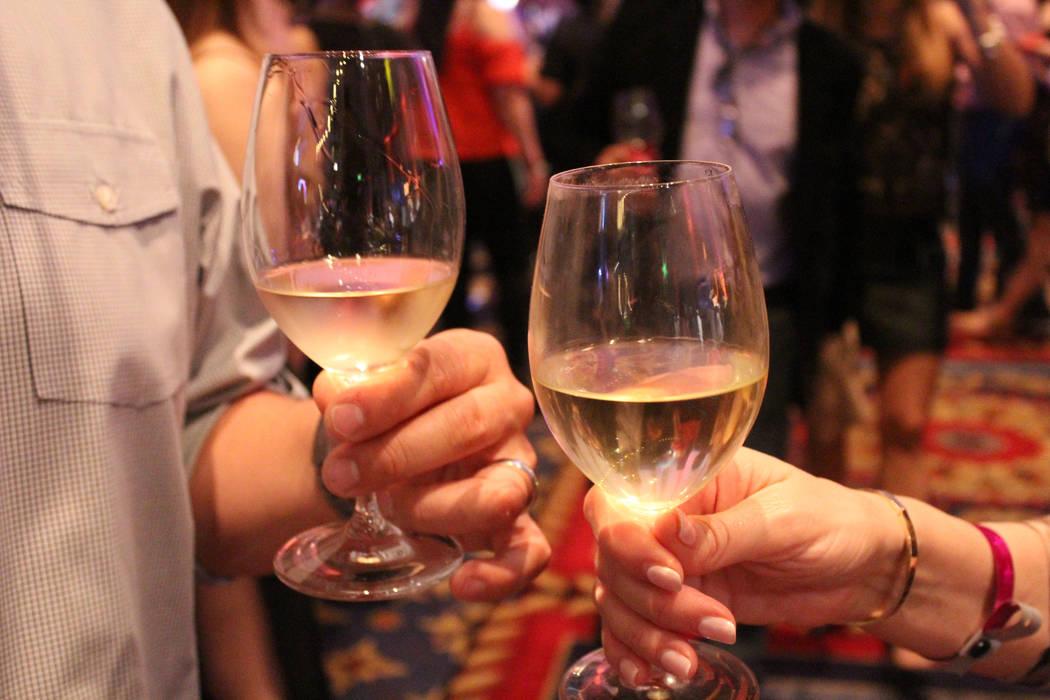 A couple clink glasses of chardonnay at UNLVino at the Paris hotel-casino, Saturday, April 1, 2017. (Gabriella Benavidez/Las Vegas Review-Journal) @gabbydeebee