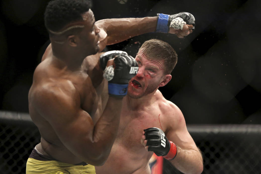 Stipe Miocic, right, lands a right hand against Francis Ngannou during a heavyweight championship mixed martial arts bout at UFC 220, early Sunday, Jan. 21, 2018, in Boston. Miocic retained his ti ...