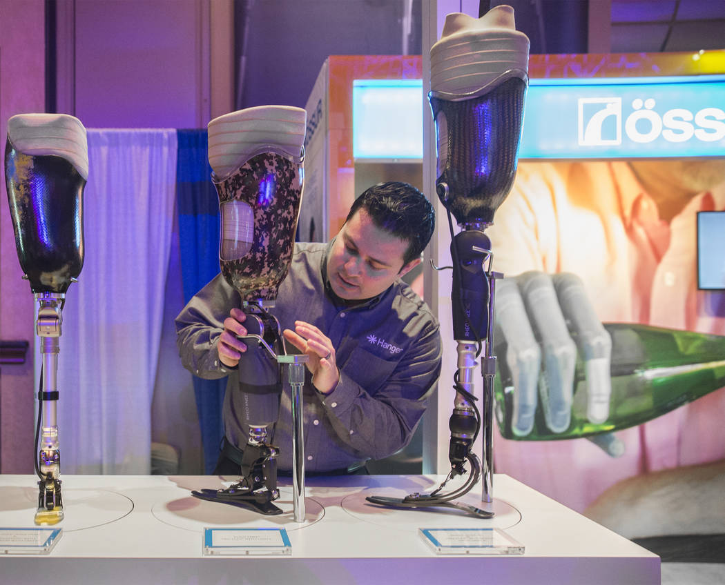 Jeffery Elms, an area clinic manager, points out features of the Rheo Knee XC at the Hanger Education Fair & National Business Meeting on Wednesday, January 31, 2018, at the Rio hotel-casino,  ...