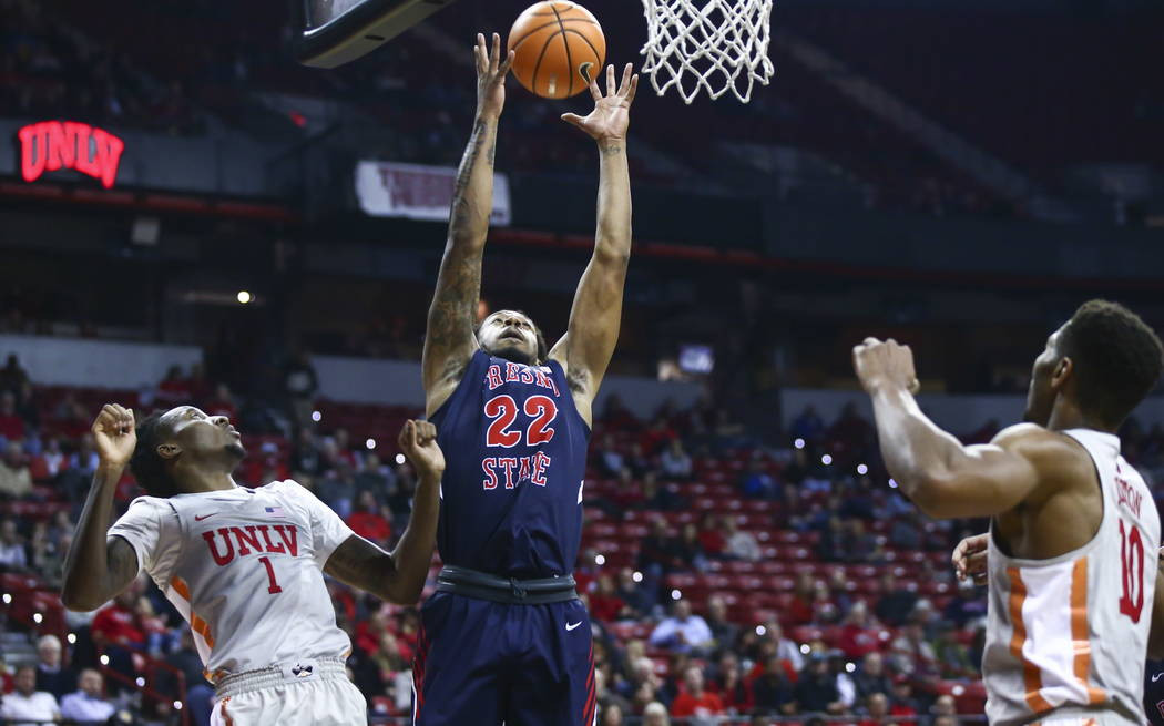 Fresno State Bulldogs guard Ray Bowles Jr. (22) gets a rebound over UNLV Rebels guard Kris Clyburn (1) and forward Shakur Juiston (10) during the first half of a basketball game at the Thomas &amp ...