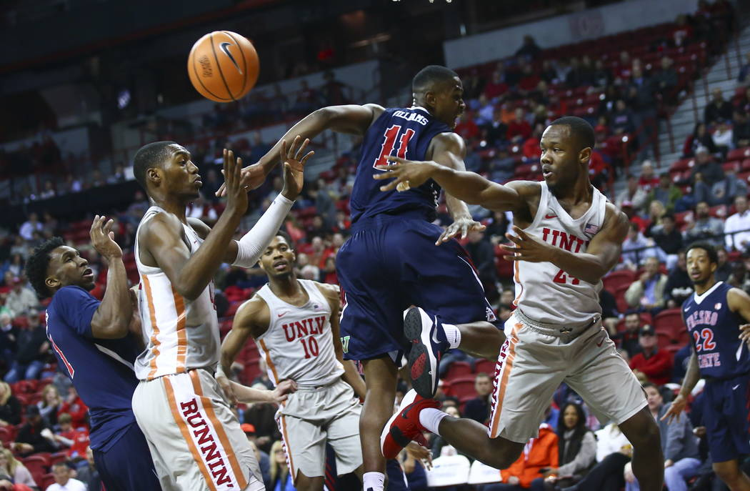 UNLV Rebels guard Jordan Johnson (24) throws the ball past Fresno State Bulldogs forward Bryson Williams (11) as UNLV Rebels forward Brandon McCoy (44), left, looks on during the second half of a  ...