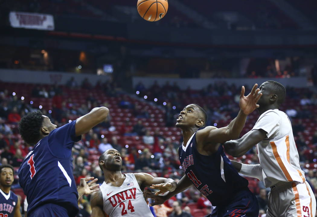 Fresno State Bulldogs forward Bryson Williams (11) and guard Jaron Hopkins (1) look to get a rebound over UNLV Rebels guard Jordan Johnson (24) forward Cheikh Mbacke Diong (34) during the first ha ...