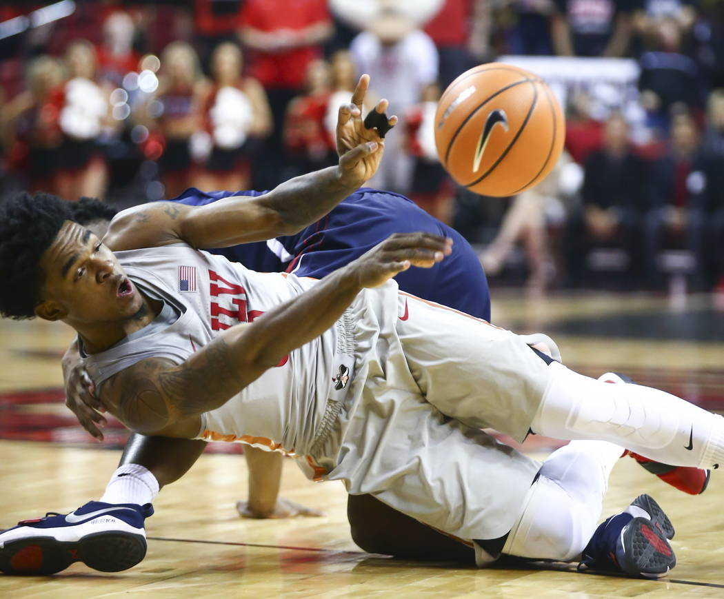 UNLV Rebels guard Jovan Mooring (30) passes the ball as he falls to the floor during the first half of a basketball game against the Fresno State Bulldogs at the Thomas & Mack Center in Las Ve ...