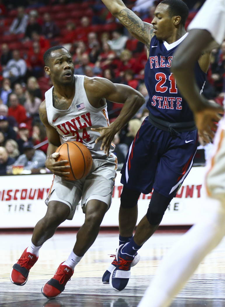 UNLV Rebels guard Jordan Johnson (24) drives against Fresno State Bulldogs guard Deshon Taylor (21) during the second half of a basketball game at the Thomas & Mack Center in Las Vegas on Wedn ...