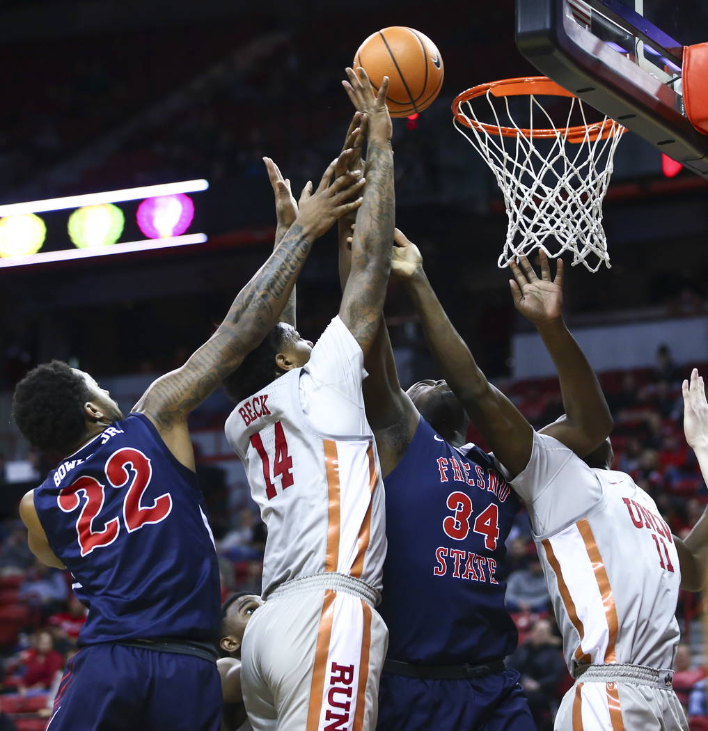 UNLV Rebels forward Tervell Beck (14) goes to the basket as Fresno State Bulldogs guard Ray Bowles Jr. (22) and Fresno State Bulldogs center Terrell Carter II (34) defend during the second half of ...
