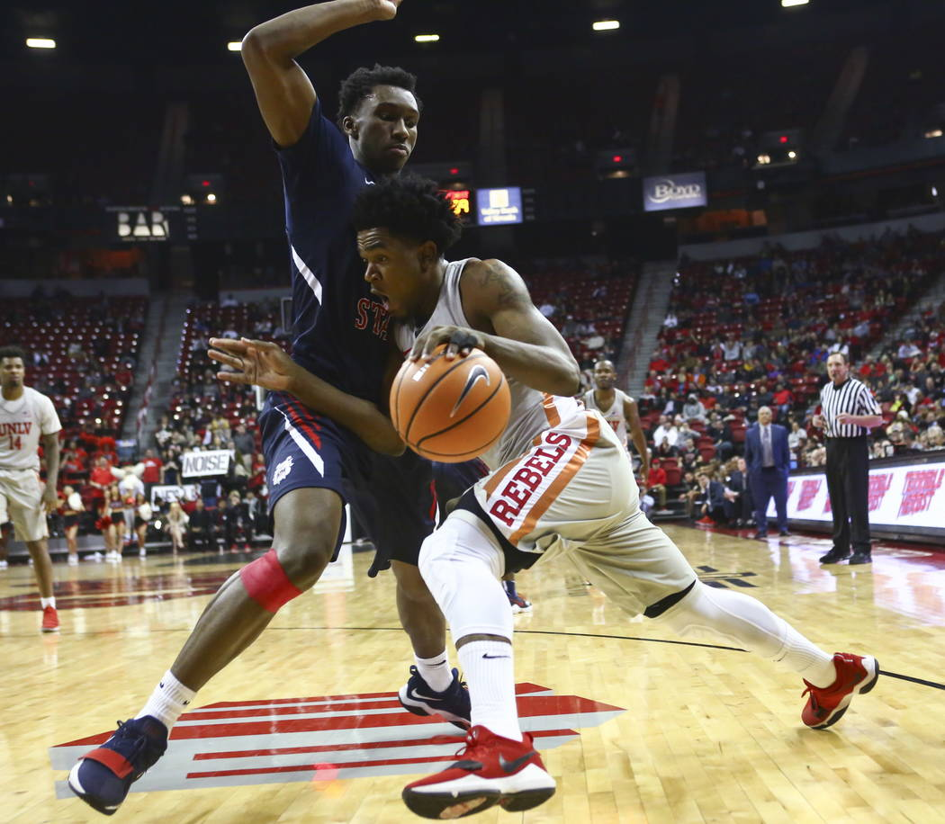 UNLV Rebels guard Jovan Mooring (30) drives against Fresno State Bulldogs guard Jaron Hopkins (1) during the first half of a basketball game at the Thomas & Mack Center in Las Vegas on Wednesd ...