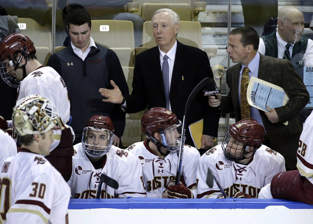 Boston College head coach Jerry York, middle, instructs his players in the second period of a regional semifinal game against Harvard in the NCAA college hockey tournament, Friday, March 25, 2016, ...