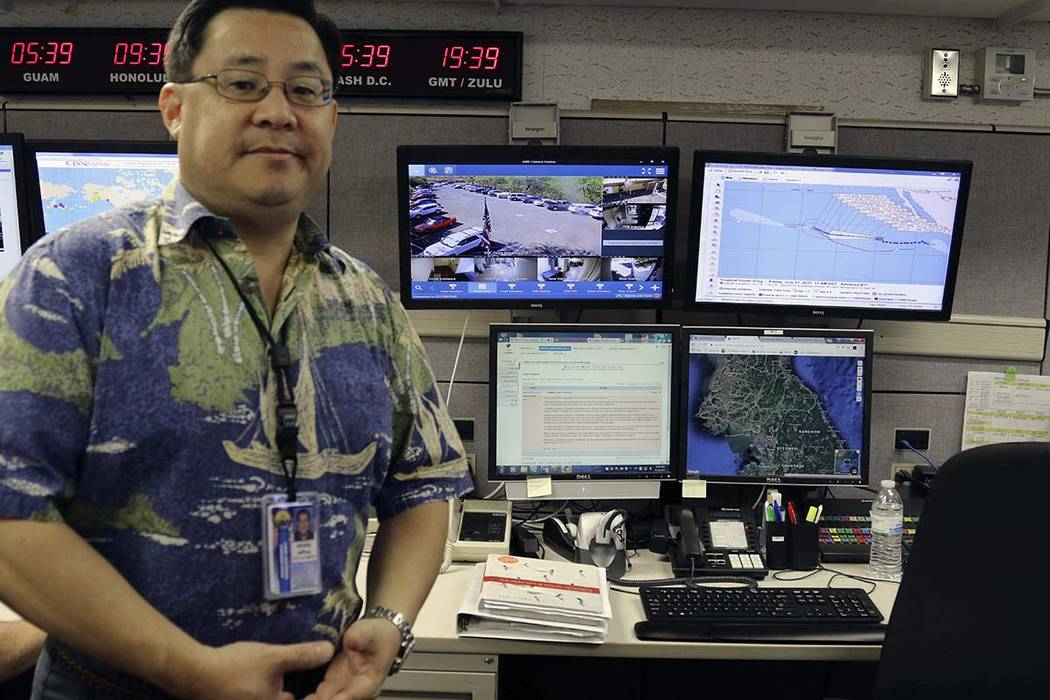 In this July 21, 2017 file photo, Jeffrey Wong, the Hawaii Emergency Management Agency's operations officer, shows computer screens monitoring hazards at the agency's headquarters in Honolulu.  (J ...