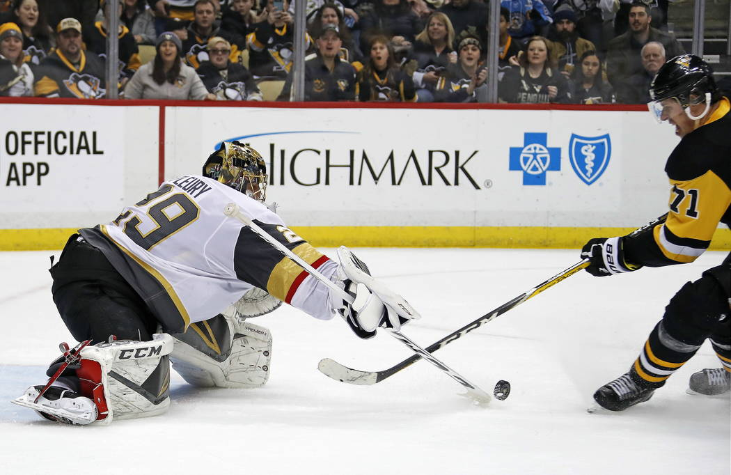 Vegas Golden Knights goaltender Marc-Andre Fleury (29) pokes the puck off the stick of Pittsburgh Penguins' Evgeni Malkin during the second period of an NHL hockey game in Pittsburgh, Tuesday, Feb ...