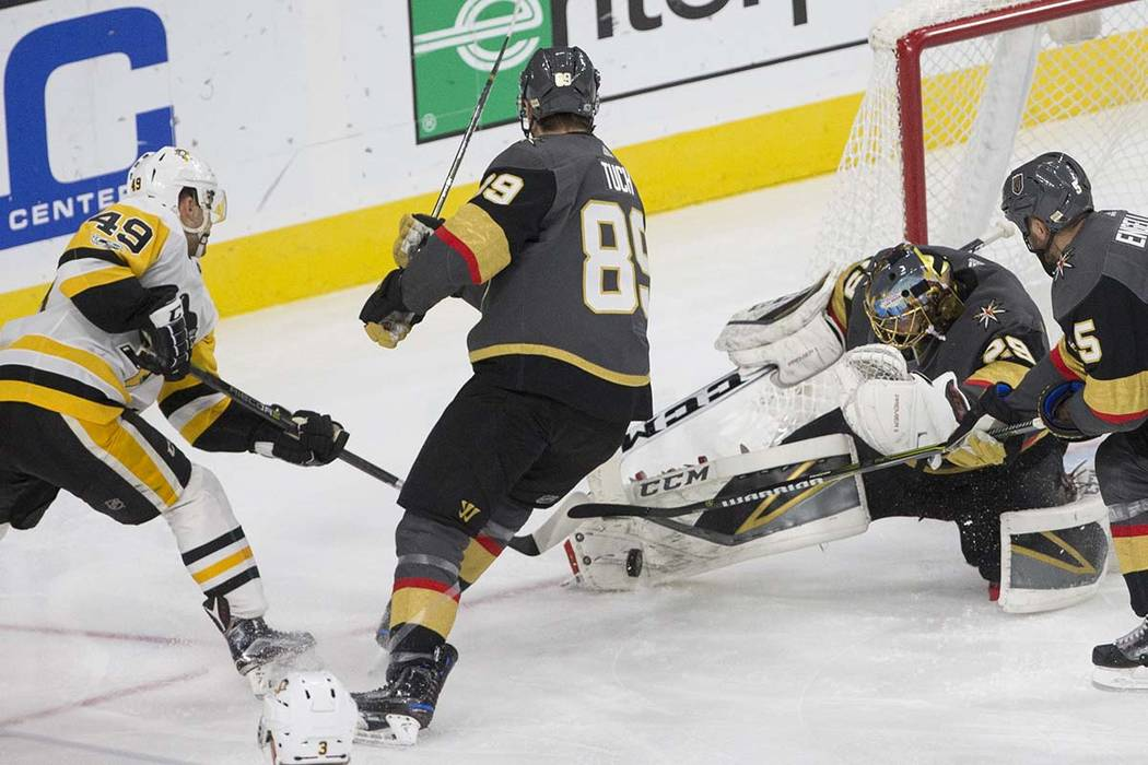 Golden Knights goaltender Marc-Andre Fleury (29) makes a save against Penguins center Dominik Simon (49) during the third period of Vegas' home matchup with Pittsburgh on Thursday, Dec. 14, 2017,  ...