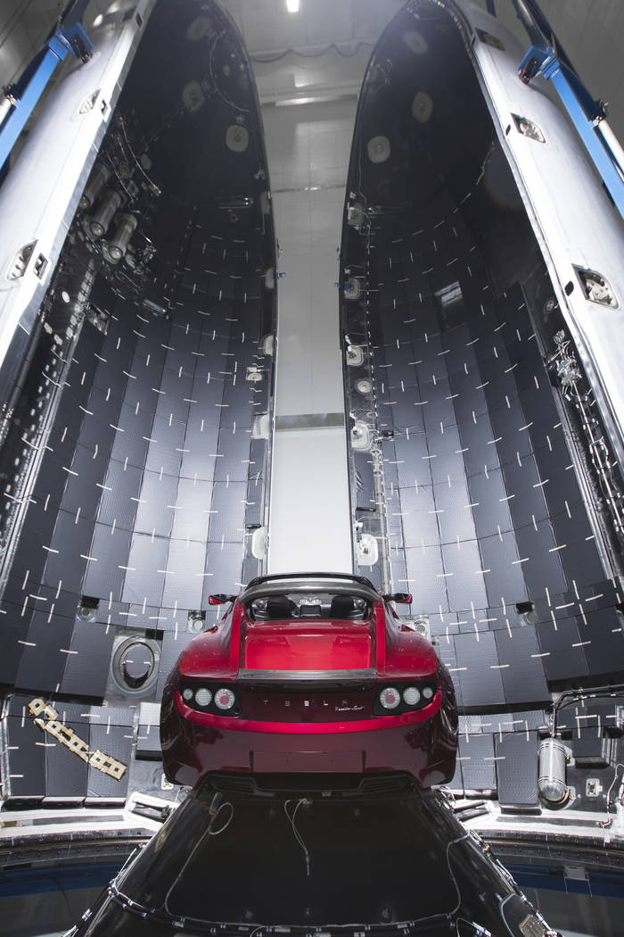 A Tesla car next to the fairing of a Falcon Heavy rocket in Cape Canaveral, Florida, Dec. 6, 2017. For the Heavy's inaugural flight, the rocket is carrying Elon Musk's roadster. (SpaceX via AP)