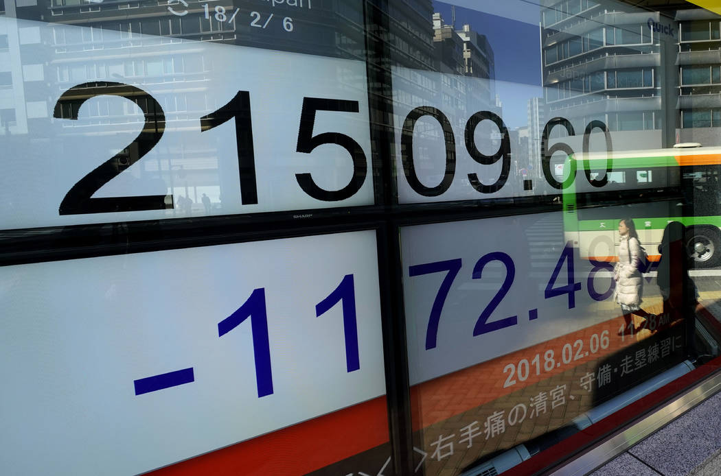People are reflected on an electronic stock indicator of a securities firm in Tokyo, Tuesday, Feb. 6, 2018. Shares tumbled in Asia on Tuesday after a wild day for U.S. markets that resulted in the ...