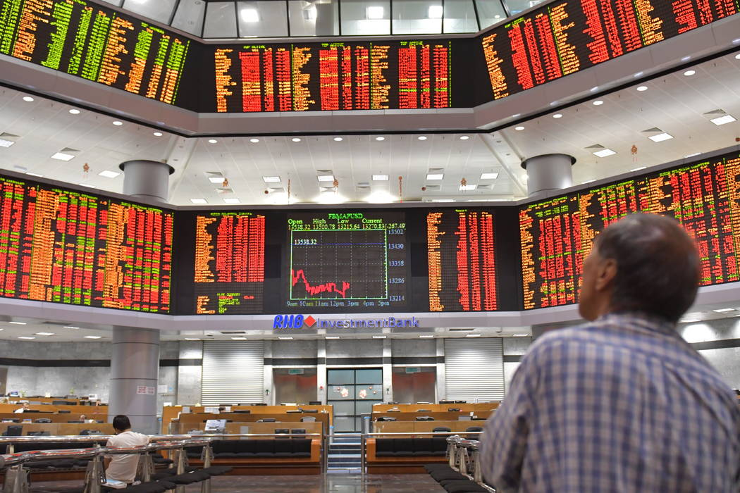 A Malaysian man watches trading boards at a private stock market gallery in Kuala Lumpur, Malaysia, Tuesday, Feb. 6, 2018. Asian markets were rattled Tuesday by the miseries on Wall Street, with J ...