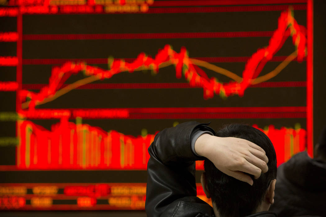 An investor monitors stock prices at a brokerage house in Beijing, Tuesday, Feb. 6, 2018. Shares tumbled in Asia on Tuesday after a wild day for U.S. markets that resulted in the biggest drop in t ...