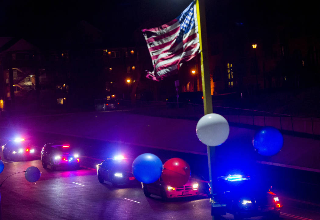 An American flag waves in the wind as a police procession travels along South Nevada Avenue for El Paso County Sheriff's Deputy Micah Flick, Monday, Feb. 5, 2018, in Colorado Springs, Colo. Flick  ...