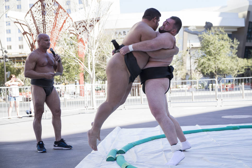 Professional sumo wrestlers from left, Robert Daniel, gives commentary as Dan Kalbfleisch is picked up off the ground by Soslan Gagloev during an Ultimate Sumo League press conference at Toshiba P ...