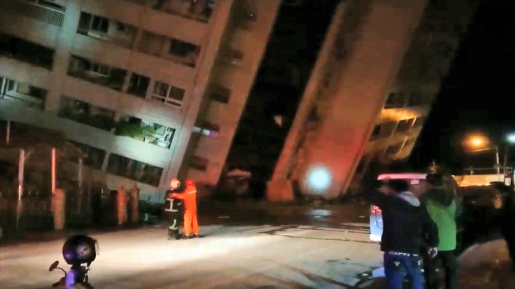 In this image from TV, emergency services attend after a building collapsed onto it's side, following an earthquake in Hualien County, eastern Taiwan, early Wednesday, Feb. 7, 2018.  A magnitude-6 ...