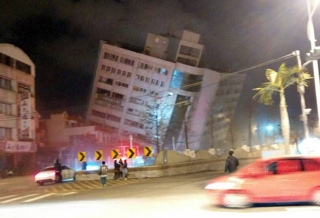 In this photo released by Hualien County Fire Bureau, rescuers are seen entering an building that collapsed onto its side from an early morning earthquake in Hualien County, eastern Taiwan, Wednes ...