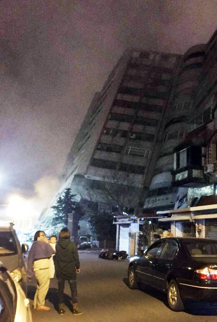 In this photo released by Hualien County Fire Bureau, Taiwanese people watching a building that collapsed on its side from an early morning earthquake in Hualien County, eastern Taiwan, early Wedn ...