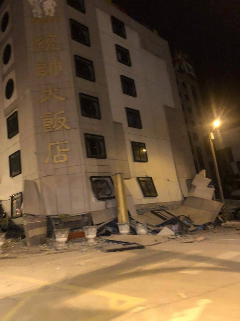 In this photo released by Hualien County Fire Bureau, debris around a building that collapsed onto its side following an early morning earthquake in Hualien County, eastern Taiwan, Wednesday, Feb. ...