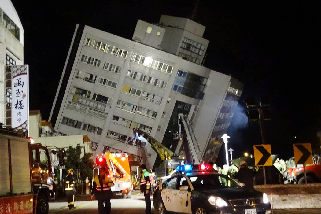 Rescuers are seen entering a building that collapsed onto its side from an early morning 6.4 magnitude earthquake in Hualien County, eastern Taiwan, Wednesday, Feb. 7 2018.  Rescue workers are sea ...