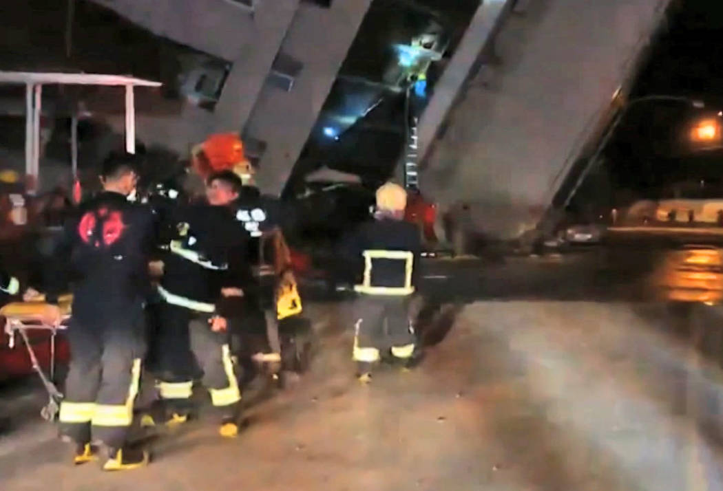 In this image from TV, emergency services attend after a building collapsed on its side, as a man climbs a ladder to gain access to the building, centre background, after an early morning earthqua ...