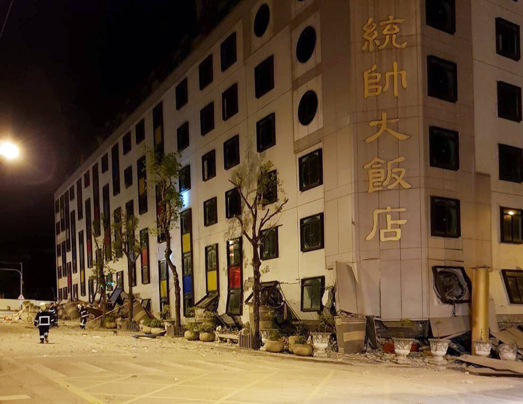 In this photo released by Hualien County Fire Bureau, debris around a building as rescue workers gain entry after the building collapsed onto its side following an early morning earthquake in Hual ...