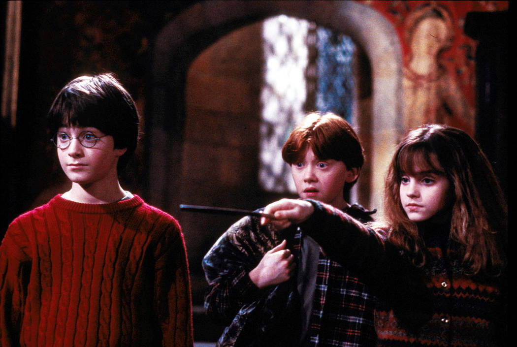 """Left to right, Harry Potter (Daniel Radcliffe), Ron Weasley (Rupert Grint) and Hermione Grainger (Emma Watson) in """"Harry Potter and the Sorcerer's Stone.""""  (Warner Bros.)"""