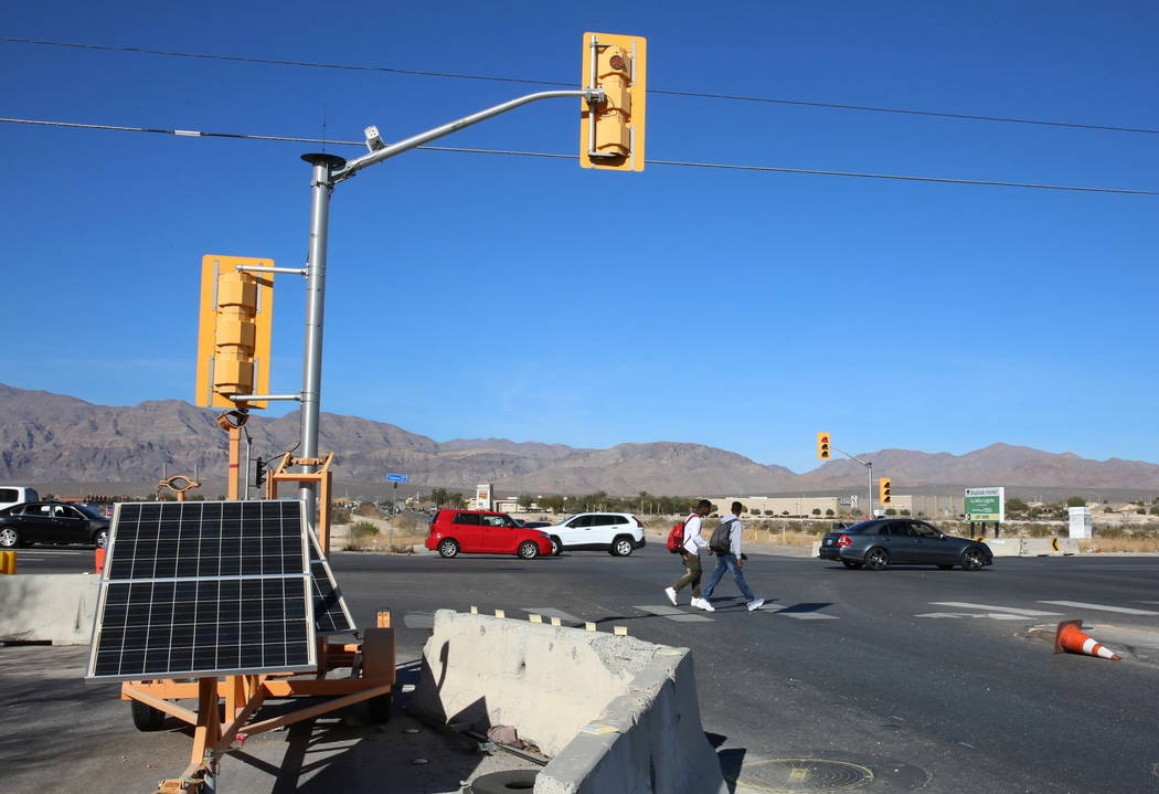 Temporary traffic signals are seen as pedestrians cross North Fifth Street, near Centennial Parkway in North Las Vegas on Thursday, Feb. 8, 2018. City officials are planning to install a traffic s ...