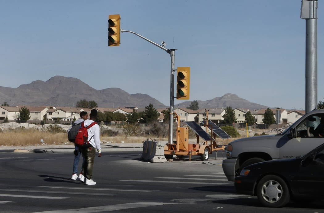 A temporary traffic signal is seen as pedestrians cross North Fifth Street, near Centennial Parkway in North Las Vegas on Thursday, Feb. 8, 2018. City officials are planning to install a traffic s ...