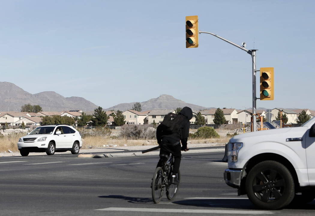 A temporary traffic signal is seen as a cyclist crosses North Fifth Street, near Centennial Parkway in North Las Vegas on Thursday, Feb. 8, 2018. City officials are planning to install a traffic s ...