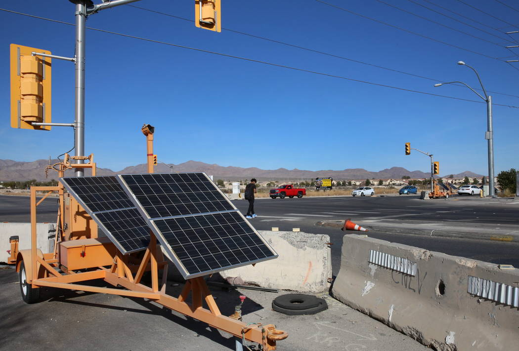 Temporary traffic signals are seen as a pedestrian crosses North Fifth Street, near Centennial Parkway in North Las Vegas on Thursday, Feb. 8, 2018. City officials are planning to install a traffi ...