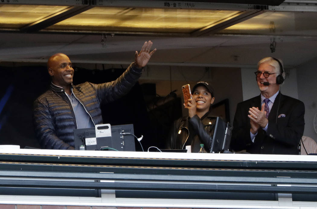 Former San Francisco Giants player Barry Bonds, left, waves to fans from the broadcast booth next to broadcaster Mike Krukow, right, during a baseball game against the Chicago Cubs, Monday, Aug. 7 ...