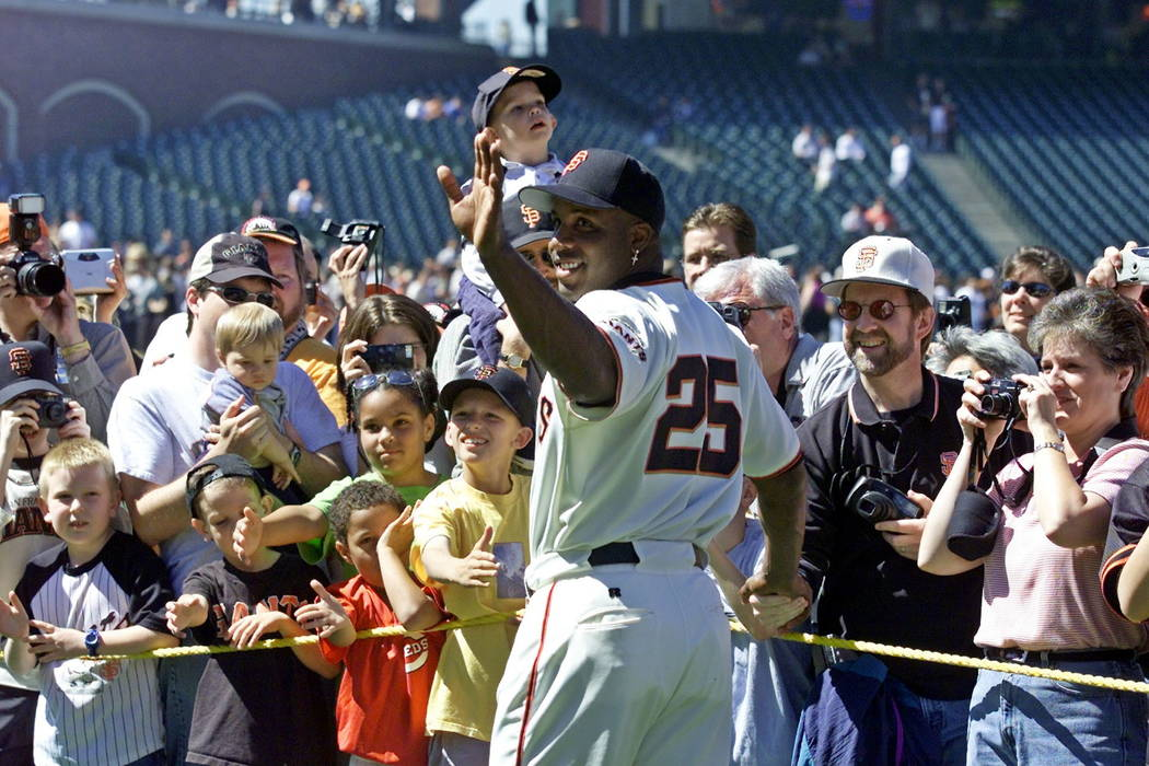 In this April 13, 2002, file photo, San Francisco Giants' Barry Bonds waves and poses for fans during the annual on-field photo day before the Giants' baseball game against the Milwaukee Brewers i ...