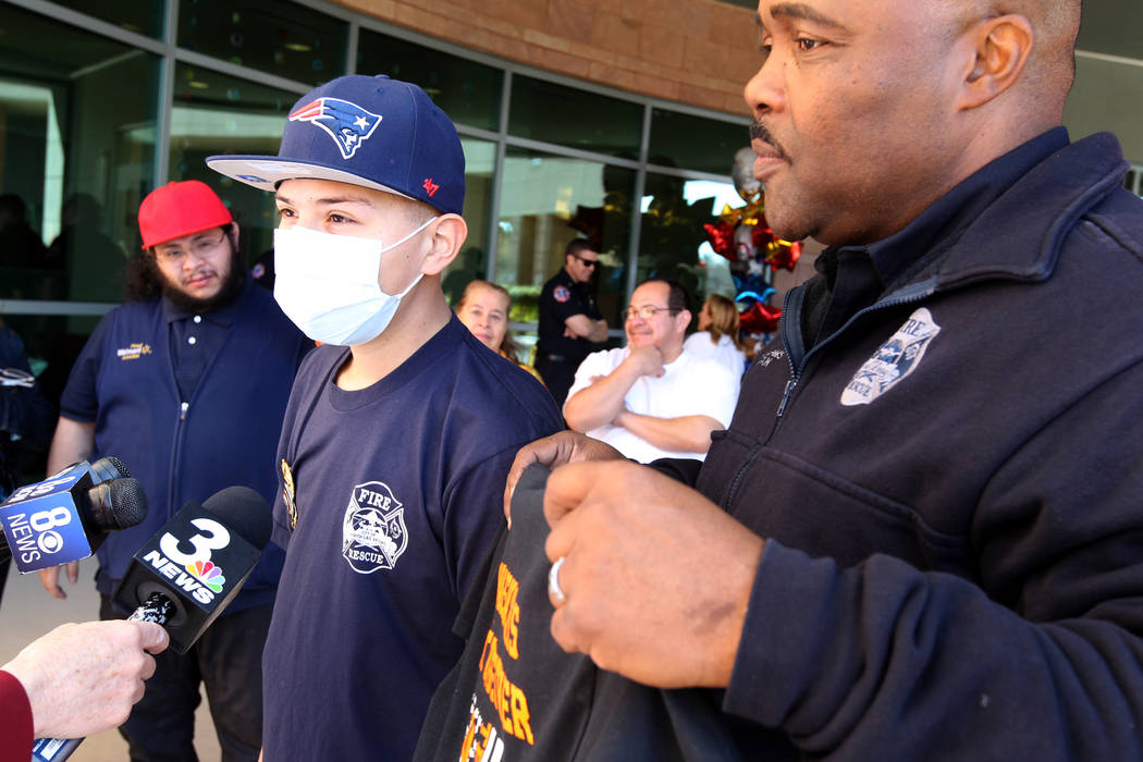 Leukemia patient Johnathan Rubio, 16, talks to the news media with Capt. Cedric Williams of the North Las Vegas Fire Department after being released from Summerlin Hospital Medical Center on Tuesd ...