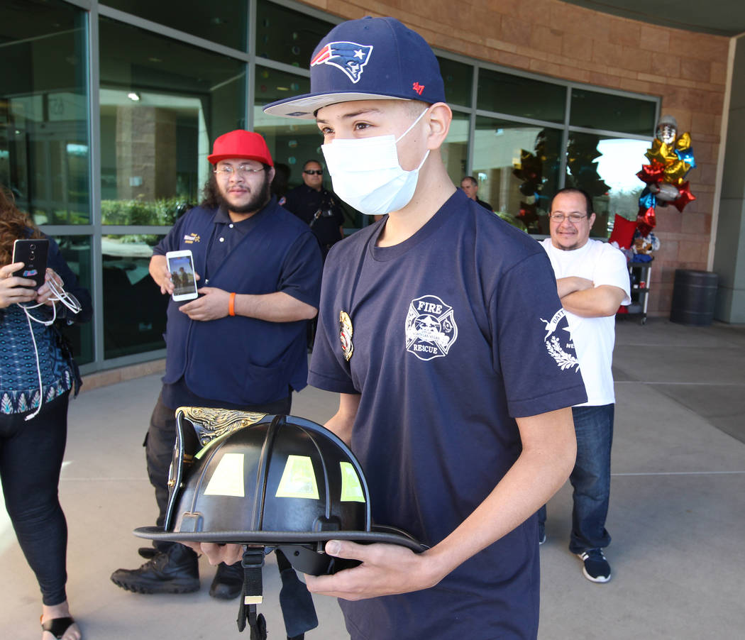 Leukemia patient Johnathan Rubio, 16, shows his North Las Vegas Fire Department helmet after being released from Summerlin Hospital Medical Center on Tuesday, Feb. 6, 2018. Rubio, who is a member  ...
