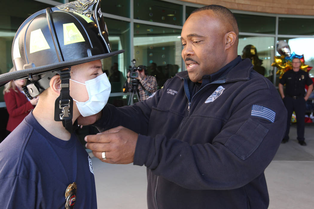 Leukemia patient Johnathan Rubio, 16, gets help with his helmet from North Las Vegas Fire Department Capt. Cedric Williams after being released from Summerlin Hospital Medical Center on Tuesday, F ...