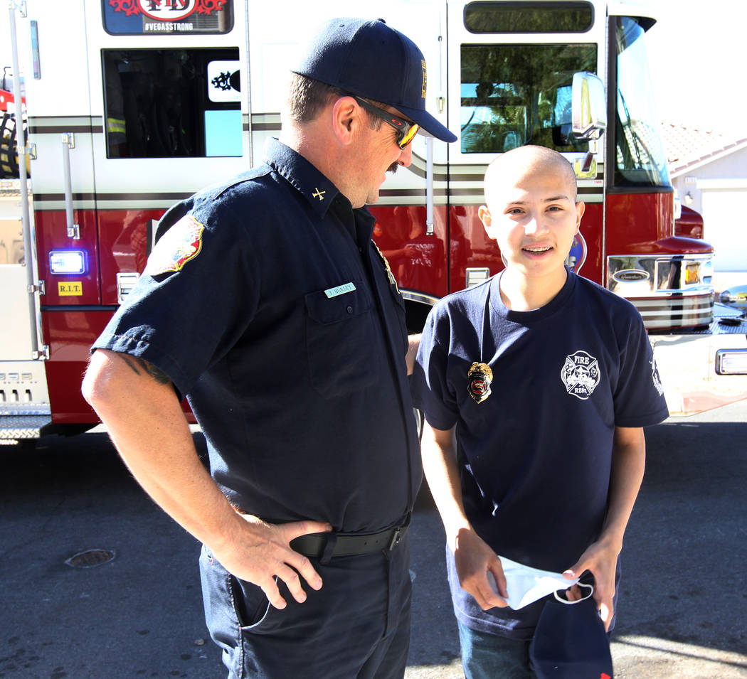 Leukemia patient Johnathan Rubio, 16, with North Las Vegas Fire Battalion Chief Jeff Hurley after getting a ride home on an engine on Tuesday, Feb. 6, 2018. Rubio, who is a member of the departmen ...