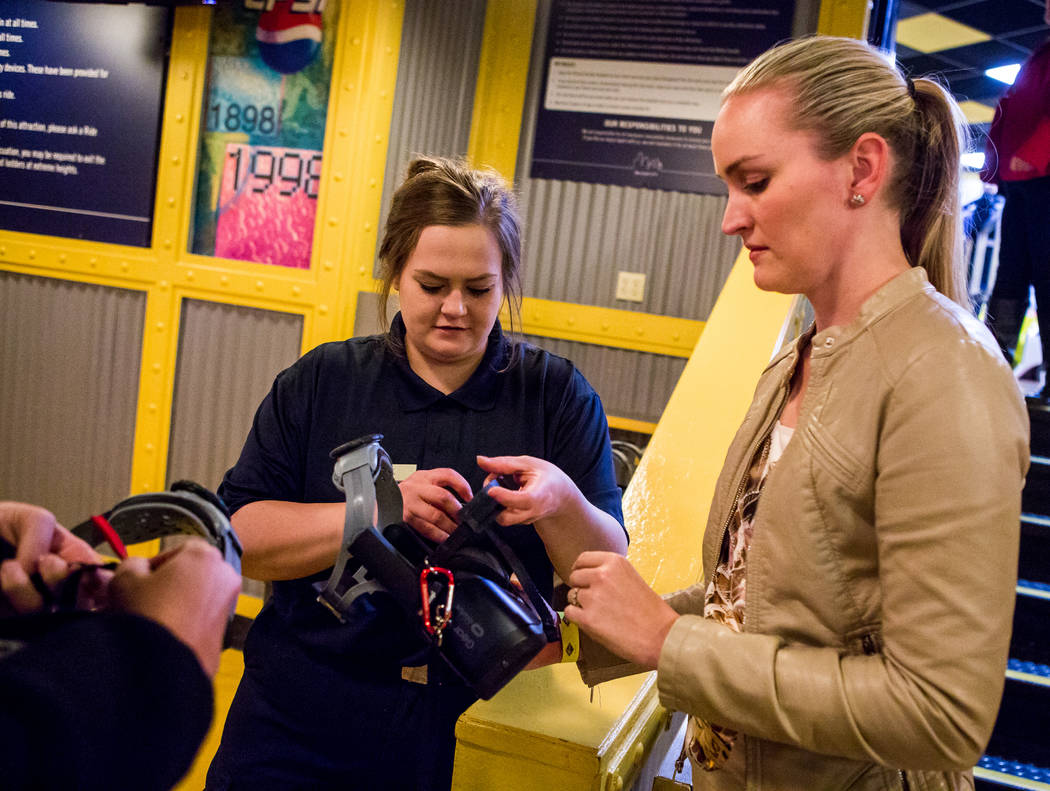 Brittany Coleman, center, helps Amanda Lewis of West Palm Beach, Fla., with her virtual reality goggles at the Big Apple Coaster at New York-New York in Las Vegas on Wednesday, Feb. 7, 2018.  Patr ...