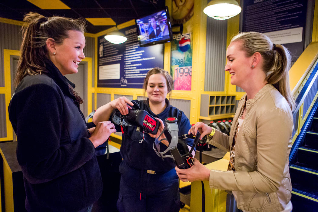 Brittany Coleman, center, helps Amanda Lewis, right, and Ashley Day of West Palm Beach, Fla., with their virtual reality goggles at the Big Apple Coaster at New York-New York in Las Vegas on Wedne ...
