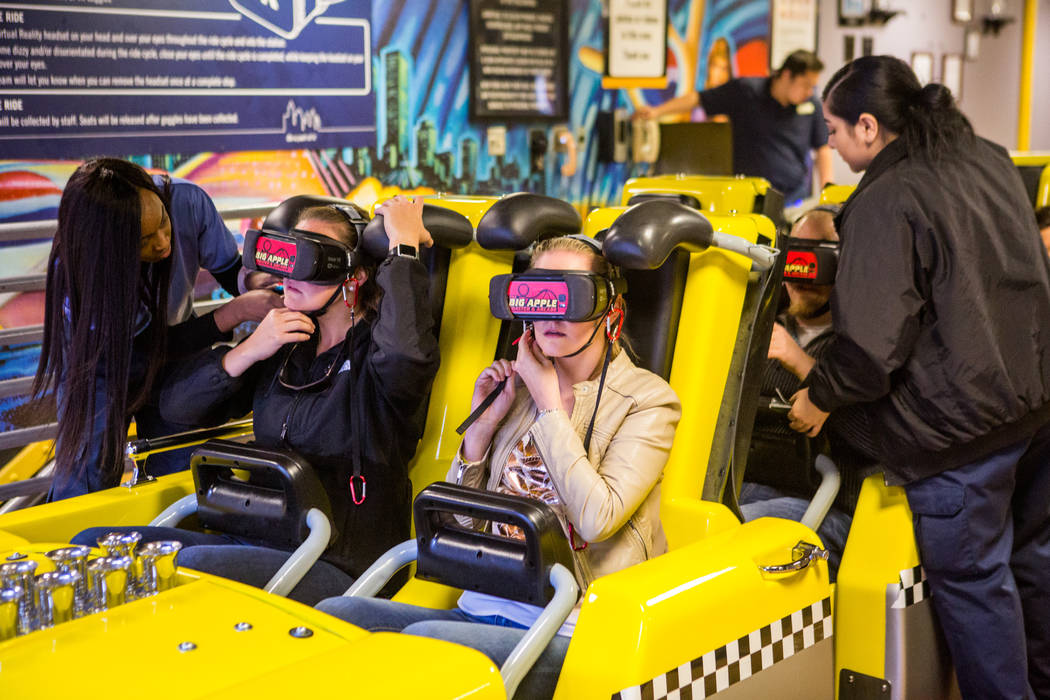 Amanda Lewis, center right, and Ashley Day, center left, of West Palm Beach, Fla., prepare to ride the Big Apple Coaster with virtual reality goggles on at New York-New York in Las Vegas on Wednes ...