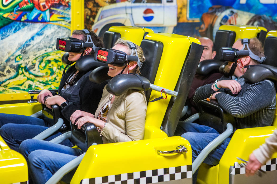 Ashley Day, left, and Amanda Lewis, second from left, of West Palm Beach, Fla., finish their ride on the Big Apple Coaster with virtual reality goggles at New York-New York in Las Vegas on Wednesd ...