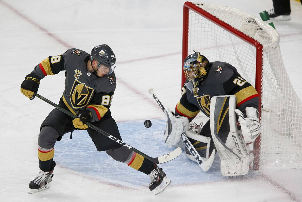 Vegas Golden Knights goaltender Marc-Andre Fleury (29) deflects the puck as Knights defenseman Nate Schmidt (88) protects the net during the third period of an NHL hockey game between the Golden K ...
