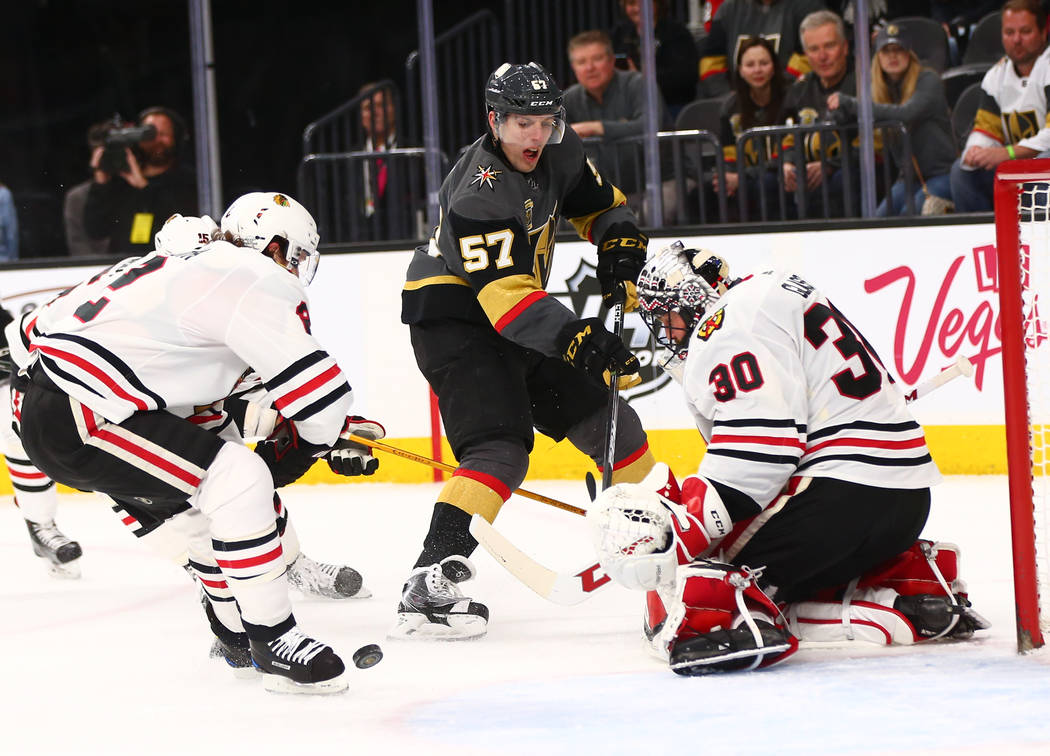 Golden Knights left wing David Perron (57) attempts to score as Chicago Blackhawks goaltender Jeff Glass (30) and  defenseman Duncan Keith (2) defend during an NHL game at T-Mobile Arena in Las Ve ...