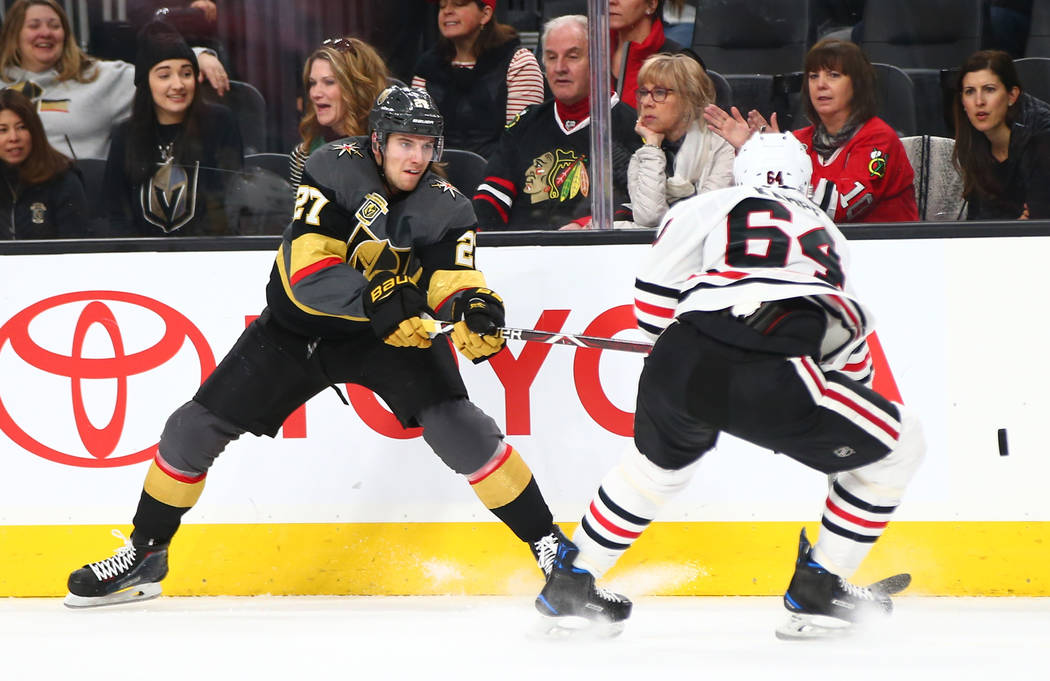 Golden Knights defenseman Shea Theodore (27) sends the puck past Chicago Blackhawks center David Kampf (64) during an NHL game at T-Mobile Arena in Las Vegas on Tuesday, Feb. 13, 2018. Chase Steve ...