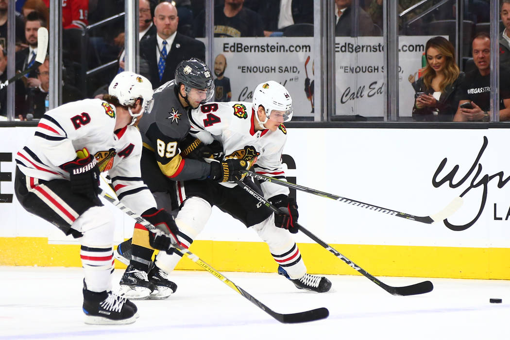 Golden Knights right wing Alex Tuch (89) fights for the puck against Chicago Blackhawks center David Kampf (64) and defenseman Duncan Keith (2) during an NHL game at T-Mobile Arena in Las Vegas on ...