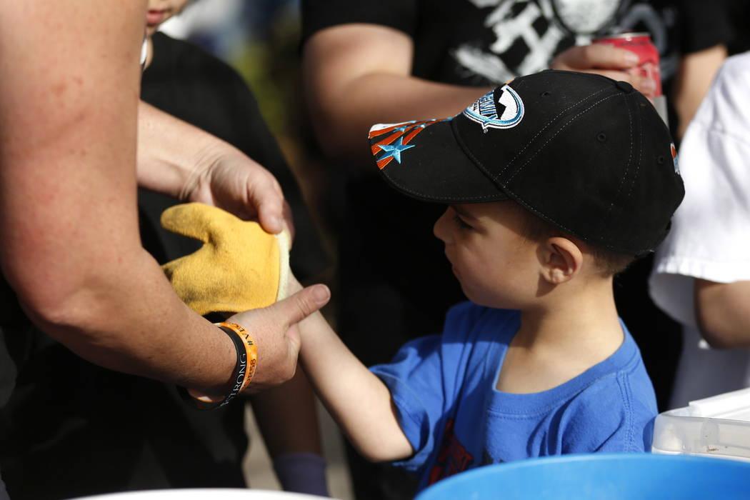 Jack Jones, 4, has his mom, Alayna Jones, help him put on gloves before helping volunteers plant 10,000 daffodils at the Healing Garden in Las Vegas on Saturday, Feb. 10, 2018. Andrea Cornejo Las  ...