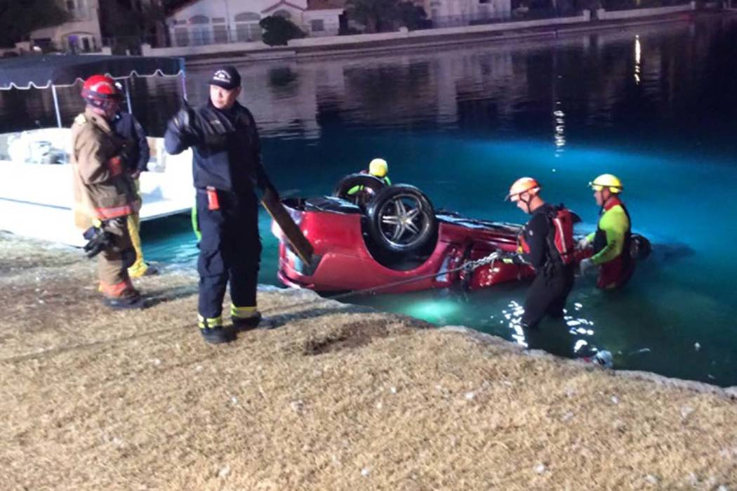 A heavy rescue team from Las Vegas Fire and Rescue recovers a submerged vehicle Thursday morning from a lake at Soaring Gulls Drive and Harbor Island. Las Vegas police confirmed that one person ha ...