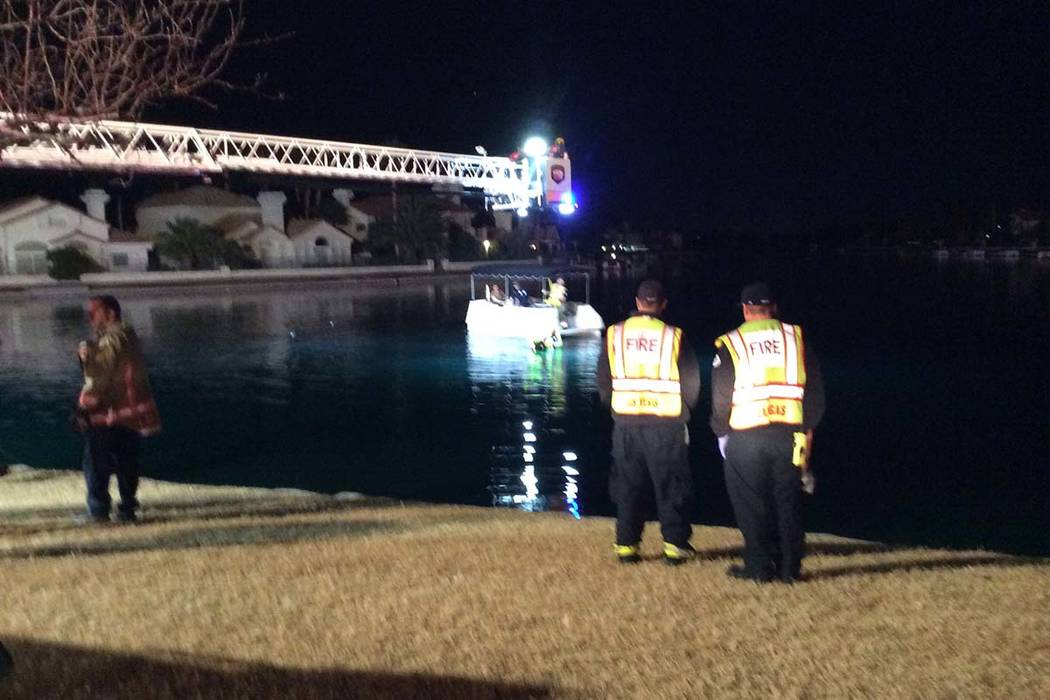 A heavy rescue team from Las Vegas Fire and Rescue recovers a submerged vehicle Thursday morning from a lake at Soaring Gulls Drive and Harbor Island. Las Vegas police confirmed one person died. ( ...