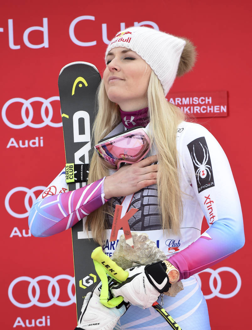 United States' Lindsey Vonn celebrates on the podium after winning an alpine ski, women's world Cup downhill race, in Garmisch Partenkirchen, Germany, Sunday, Feb. 4, 2018. (AP Photo/Marco Tacca)